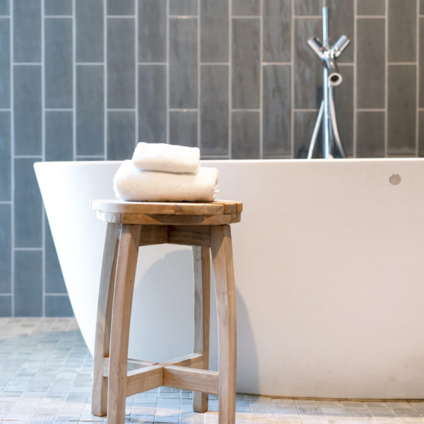 Freestanding bathtub in modern bathroom with grey subway tile