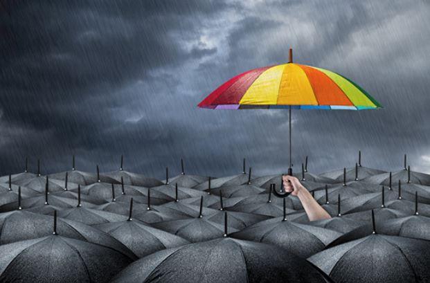 Colorful umbrella in a sea of black umbrellas